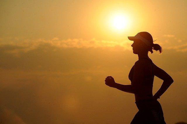 žena běžící při západu slunce